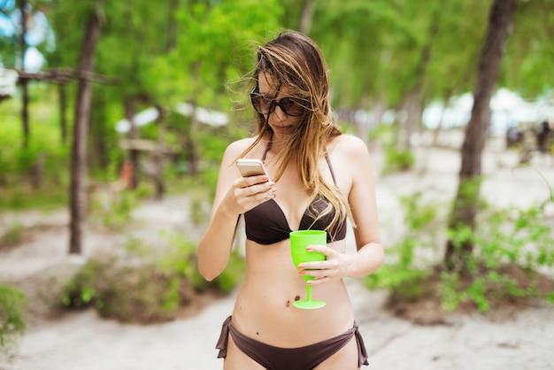 Hübsches mädchen im braunen bikini, das internet surft, das ausgefallenes glas hält