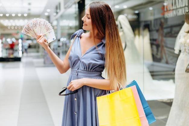Hübsches mädchen im einkaufszentrum gibt geld aus