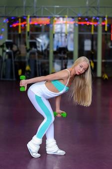 Hübsches mädchen im fitnessstudio beschäftigt sich mit fitness.