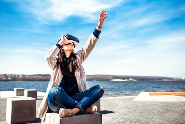 Hübsches mädchen im freien, das gläser der virtuellen realität genießt