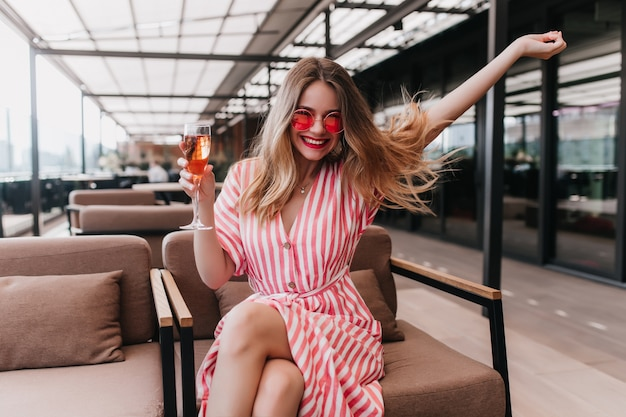 Hübsches mädchen im gestreiften kleid, das positive emotionen am sommertag ausdrückt. innenfoto des wunderbaren weiblichen modells trägt rosa sonnenbrille, die glas champagner hält.