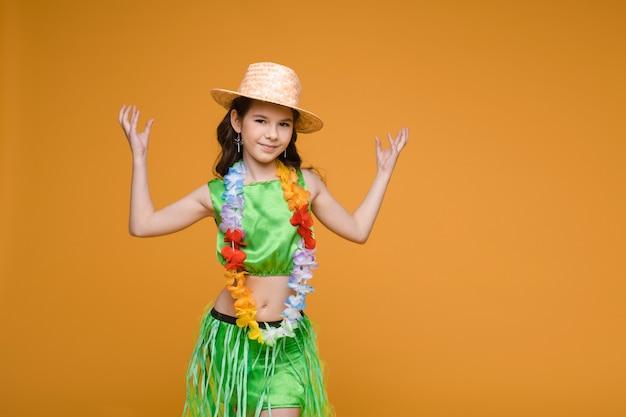 Hübsches mädchen im hawaiianischen kostüm und im hut.