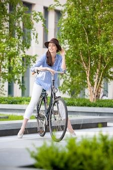 Hübsches mädchen im hut, der ein fahrrad an der straße reitet