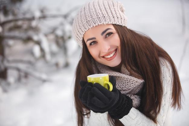 Hübsches mädchen im wald im winter mit teeschale.