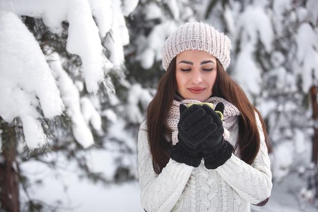 Hübsches mädchen im wald im winterhintergrund mit teeschale. trinkender kaffee der schönen netten frau draußen. schließen sie herauf porträt einer schönen dame