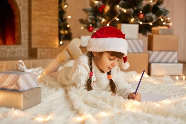 Hübsches mädchen im weihnachtshut schreibt brief an den weihnachtsmann, während es auf weißem teppich auf dem boden liegt