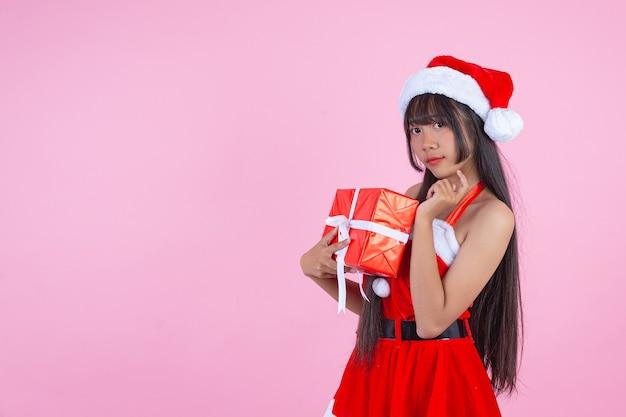 Hübsches mädchen im weihnachtskostüm, das weihnachtsgeschenk hält