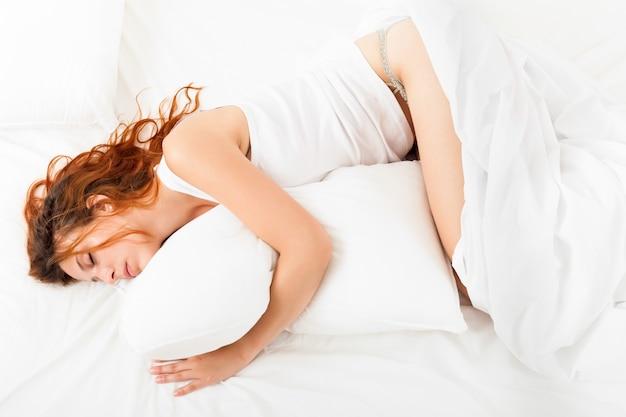 Hübsches mädchen im weißen hemd schlafend mit weißem kissen