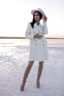 Hübsches mädchen im weißen mantel in den winterschuhen europäisches mädchen im mantel lächelt an einem kalten tag fröhliche brünette dame, die spaß während des modernen fotoshootings salzsee hat