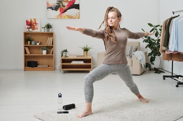 Hübsches mädchen in der aktivkleidung, die beine und arme streckt, während auf freizeit auf teppich trainiert