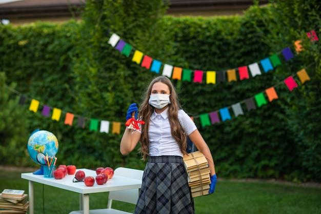Hübsches mädchen in der schuluniform an der medizinischen maske und an den handschuhen, die mit schulglocke und büchern aufwerfen