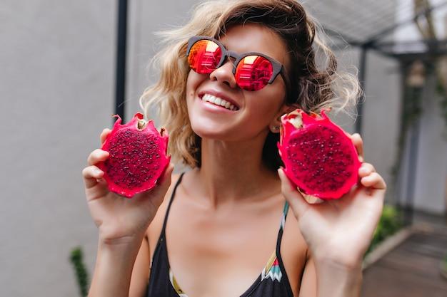 Hübsches mädchen in der stilvollen funkelnden brille, die spaß am sommerresort hat. wunderbare blonde dame, die rote pitahaya hält und lacht.