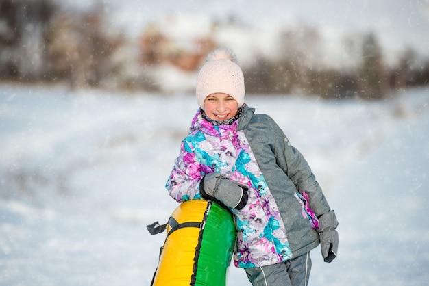 Hübsches mädchen in der warmen kleidung mit aufblasbarem schneeschlitten, der am wintertag bergab steht