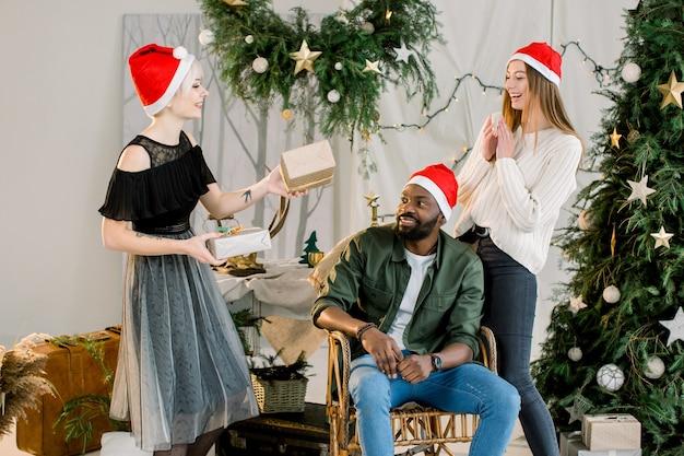 Hübsches mädchen in der weihnachtsmütze gibt ihren freunden afrikanischen mann und kaukasische frau geschenke