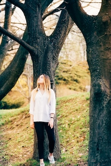 Hübsches mädchen in einem park mit großen märchenbäumen
