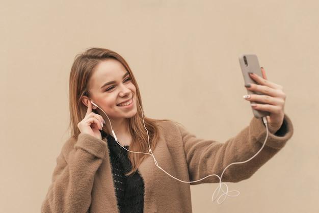 Hübsches mädchen in einem stilvollen frühlingskleid, einen mantel tragend, musik in den kopfhörern hörend, lächelnd und selfie auf dem hintergrund einer beigen wand machend