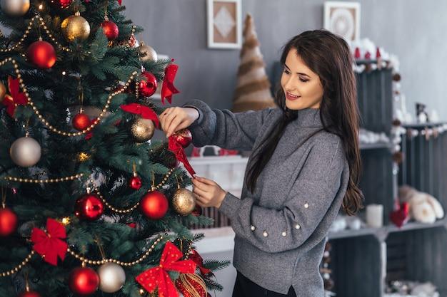Hübsches mädchen in einer grauen strickjacke wirft vor einem weihnachtsbaum mit roten spielwaren auf