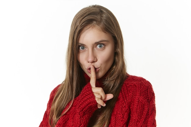 Hübsches mädchen in gestricktem pullover, das vorderfinger an ihren lippen hält und mit spielerischem geheimnisvollem gesichtsausdruck schaut, shh, lass es uns geheim halten. gesten, zeichen und körpersprache