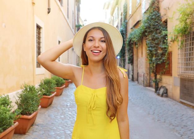 Hübsches mädchen in trastevere, rom. schöne modefrau mit gelbem kleid und hut geht durch die straßen von rom, italien.