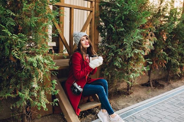 Hübsches mädchen in voller länge in rotem mantel, gestrickter mütze und weißen handschuhen, die auf holztreppen zwischen grünen zweigen im freien sitzen. sie hält kaffee zum mitnehmen und lächelt.