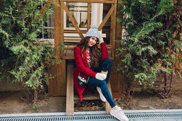 Hübsches mädchen in voller länge mit langen haaren im roten mantel und gestrickter mütze, die auf holztreppen im freien sitzt. sie hält kamera und kaffee in weißen handschuhen und lächelt.
