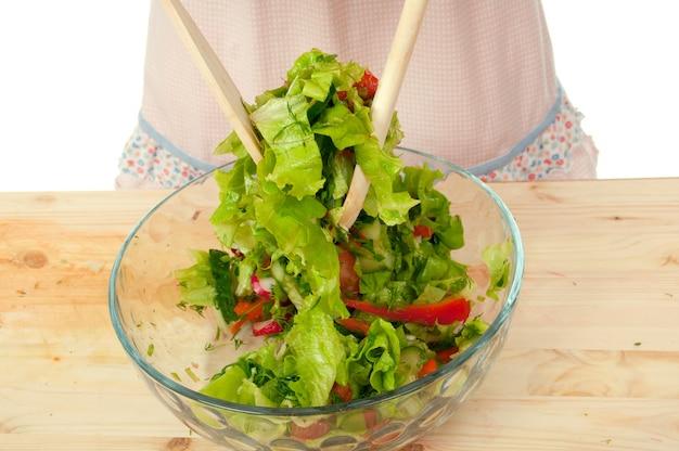 Hübsches mädchen mischen einen salat .studio, weißer hintergrund. gesunder vegetarischer salat