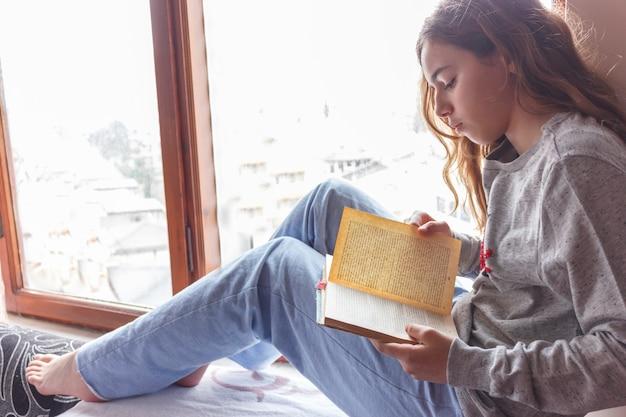 Hübsches mädchen mit dem langen haar ein buch nahe fenster lesend