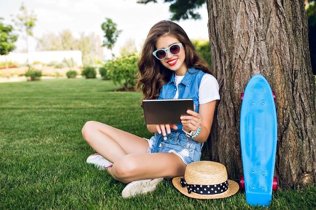 Hübsches mädchen mit dem langen lockigen haar in der sonnenbrille sitzt nahe baum im sommerpark. sie trägt jeansshorts, wams und turnschuhe. sie hält die beine gekreuzt und benutzt eine tablette in den händen.