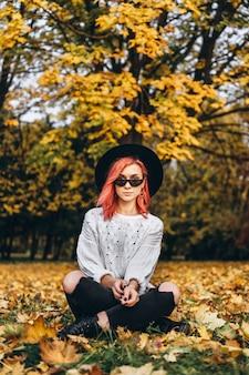 Hübsches mädchen mit dem roten haar und hut, die im park, herbstzeit sich entspannt.