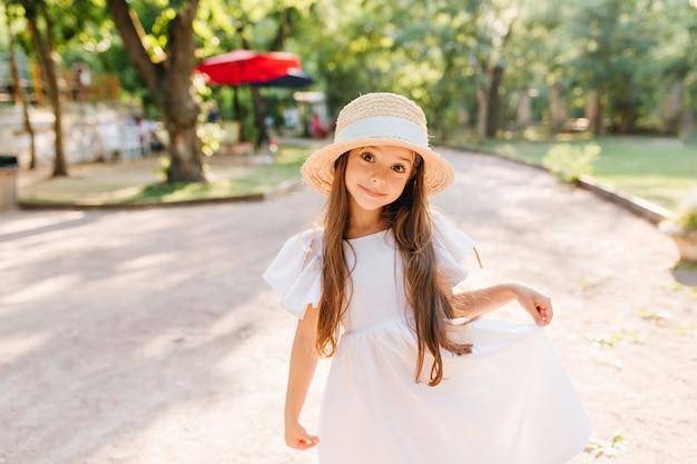 Hübsches mädchen mit den schönen großen dunklen augen, die beim spaß im park in den sommerferien aufwerfen. außenporträt des lustigen langhaarigen kindes im strohhut, das auf der straße mit überraschtem lächeln steht.