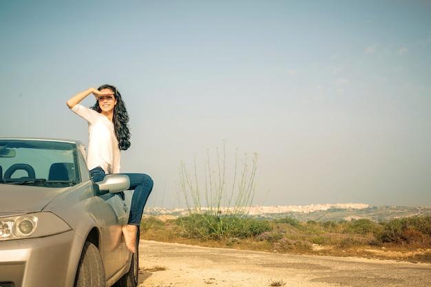 Hübsches mädchen mit einem cabrio-auto