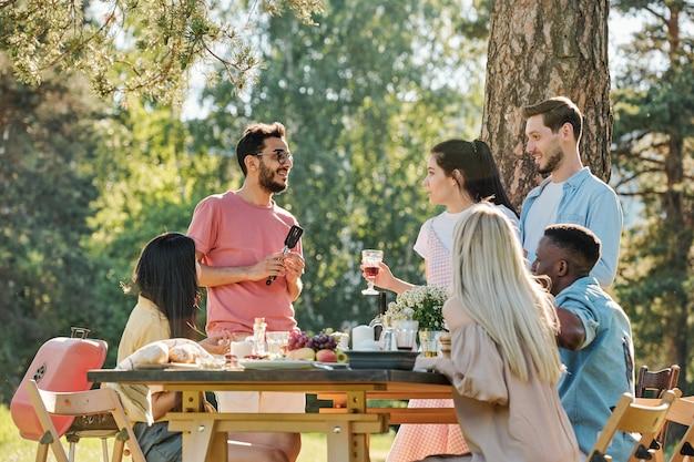 Hübsches mädchen mit einem glas rotwein, das neben ihrem freund steht und mit einem freund gemischter rassen spricht, indem es festlichen tisch während des abendessens im freien serviert