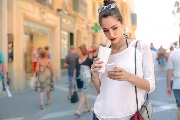 Hübsches mädchen mit einem kaffee zum mitnehmen, der ihren smartphone überprüft