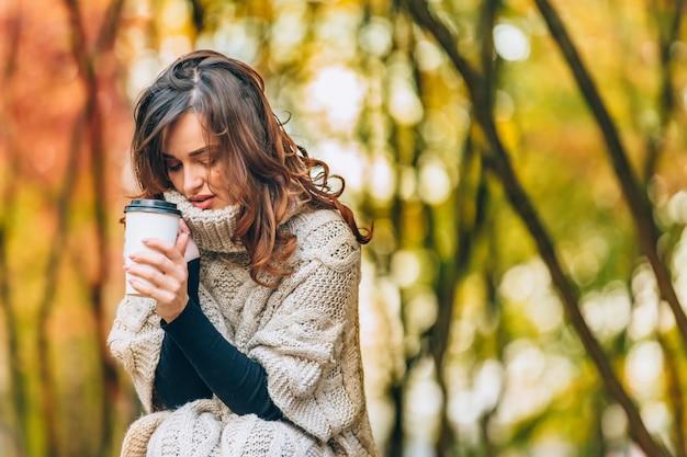 Hübsches mädchen mit einer tasse heißem getränk lächelt im herbst im wald. frau in einem warmen pullover