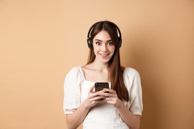 Hübsches mädchen mit kopfhörern, das in die kamera lächelt, musik hört und beigefarbenem hintergrund der handy-app verwendet