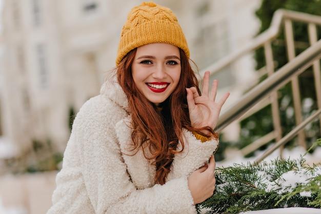 Hübsches mädchen mit langen dunklen haaren, die im winter lachen. außenaufnahme der romantischen kaukasischen frau, die im kalten tag kühlt.