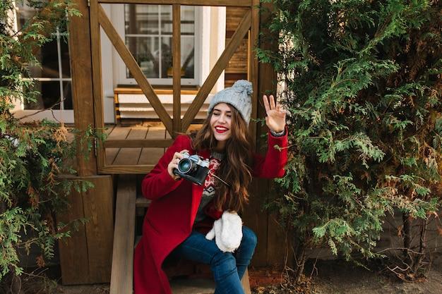 Hübsches mädchen mit langen haaren im roten mantel und gestrickter mütze, die auf holztreppen sitzt. sie hält die kamera und schaut zur seite.