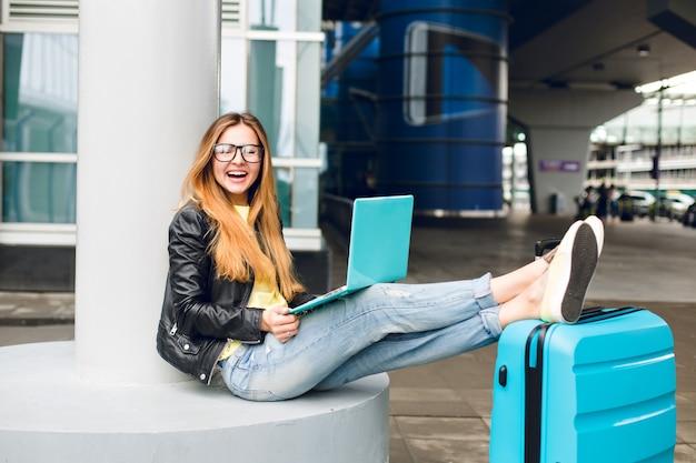 Hübsches mädchen mit langen haaren in der brille sitzt draußen im flughafen. sie trägt jeans, schwarze jacke, gelbe schuhe und einen laptop. sie legte ihre beine auf den koffer und lächelte in die kamera.