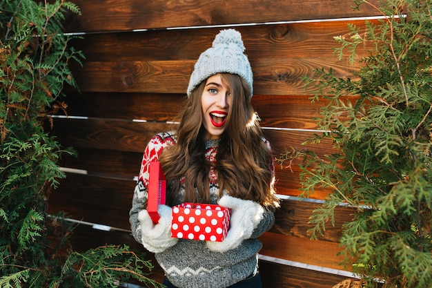 Hübsches mädchen mit langen haaren in der winterkleidung auf holz. sie hält weihnachtsgeschenk in handschuhen und sieht erstaunt aus.