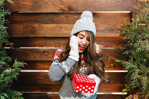 Hübsches mädchen mit langen haaren in der winterkleidung auf holz. sie hält weihnachtsgeschenk und sieht überrascht aus.