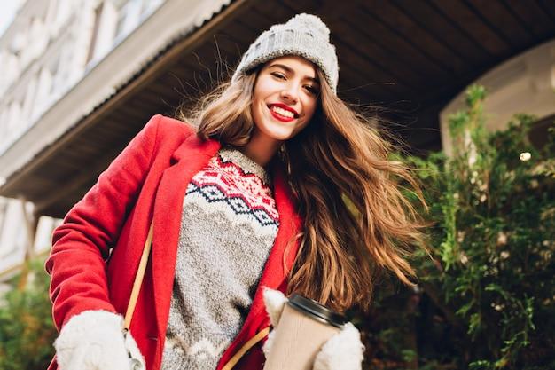 Hübsches mädchen mit langen haaren in strickmütze, roter mantel, der mit kaffee auf straße geht. sie trägt weiße handschuhe und bewegt sich hinter der kamera.