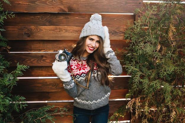 Hübsches mädchen mit langen haaren in strickmütze und handschuhen auf holz. sie trägt einen pullover, hält die kamera und lächelt.