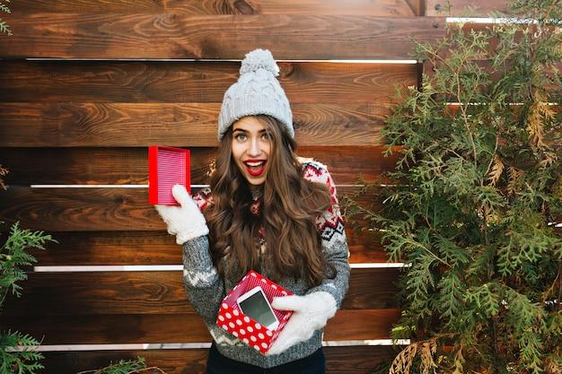 Hübsches mädchen mit langen haaren in strickmütze und warmem pullover auf holz. sie hält weihnachtsgeschenk mit telefon in handschuhen und sieht erstaunt aus.