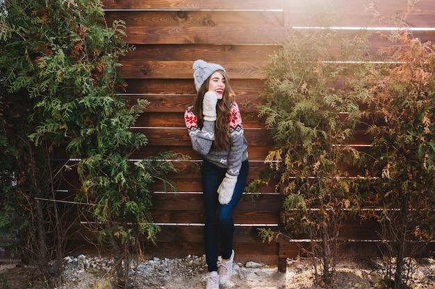 Hübsches mädchen mit langen haaren in strickmütze und warmen handschuhen auf holz. sie lächelt zur seite.
