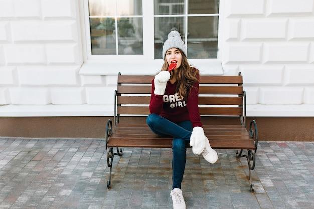 Hübsches mädchen mit langen haaren in strickmützenjeans, weiße handschuhe, die auf bank auf straße sitzen. sie sieht erfreut aus, karamellherz zu lecken.