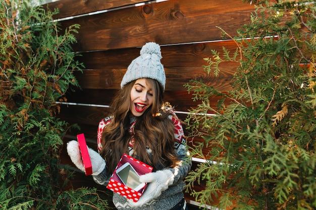 Hübsches mädchen mit langen haaren in winterkleidung auf grünen blättern der hölzernen außeneinfassung. sie hält weihnachtsgeschenk in handschuhen und sieht erstaunt aus.
