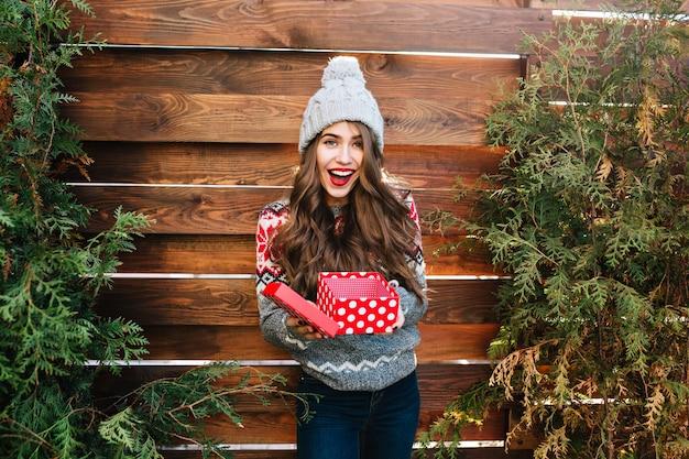 Hübsches mädchen mit langen haaren mit weihnachtskiste auf holz. sie trägt warme winterkleidung, eine strickmütze und lächelt glücklich.