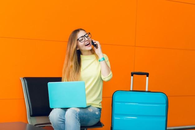 Hübsches mädchen mit langen haaren sitzt auf stuhl auf orange hintergrund. sie hat einen blauen laptop auf den knien und einen blauen koffer in der nähe. sie spricht am telefon.