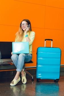 Hübsches mädchen mit langen haaren sitzt auf stuhl auf orange hintergrund. sie trägt jeans mit gelbem pullover. sie hat einen laptop und einen koffer in der nähe. sie spricht am telefon.