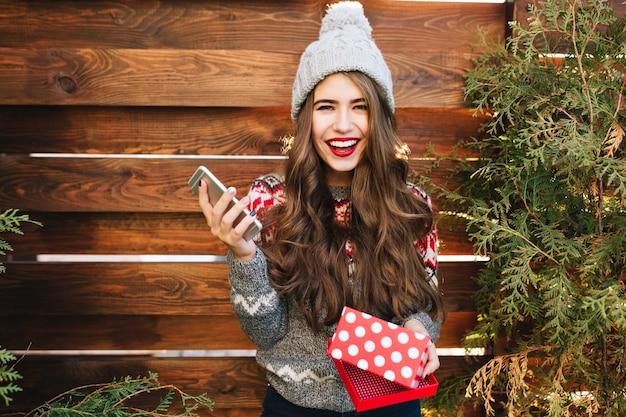 Hübsches mädchen mit langen haaren und roten lippen mit weihnachtsbox und telefon auf holz. sie trägt warme winterkleidung und lächelt.